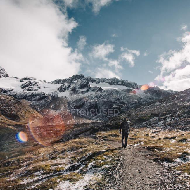 Vista posterior de caminante caminando en la montaña Nevada - foto de stock