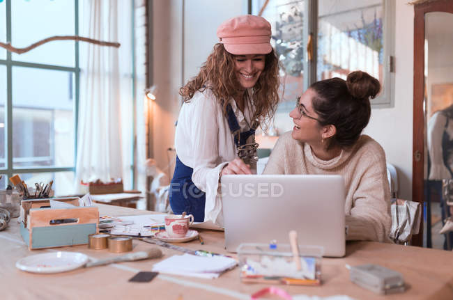 Cheerful women using laptop in shop — Stock Photo