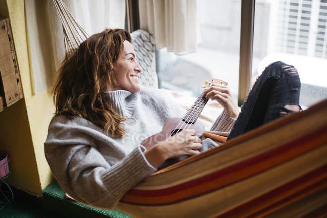 Brunette woman in hammock playing ukulele — Stock Photo