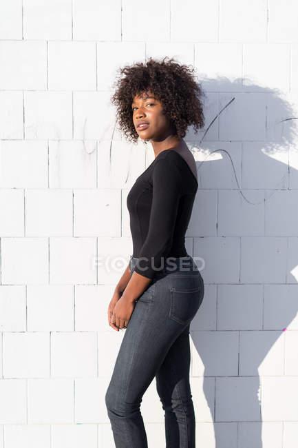 Vista lateral de la mujer posando en la pared blanca y mirando a la cámara - foto de stock