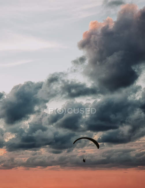 Silueta del hombre parapente sobre el cielo nublado de la noche . - foto de stock