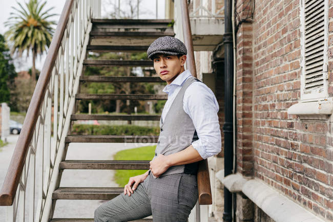 Cheerful man in vintage clothes and cap posing  on stairs — Stock Photo