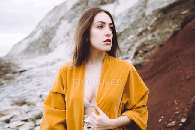 Gentle brunette in yellow jacket posing on shore — Stock Photo