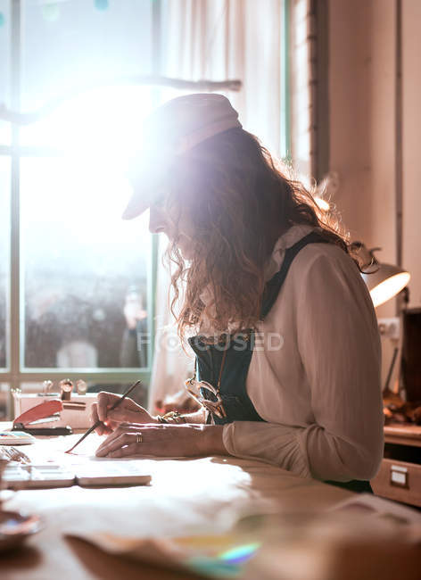 Side view of curly painter with brush attable — Stock Photo