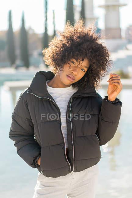 Stylish curly woman posing at urban pond — Stock Photo