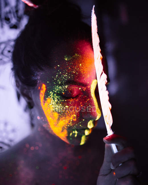 Pretty woman with fluorescent paint on face and illuminated feather. — Stock Photo