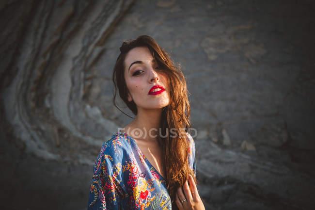 Brunette en robe posant contre les rochers — Photo de stock