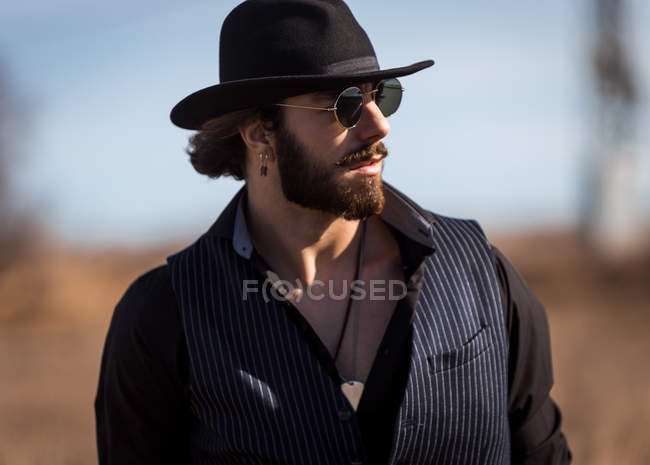 Stylish man in hat and sunglasses posing on field — Stock Photo