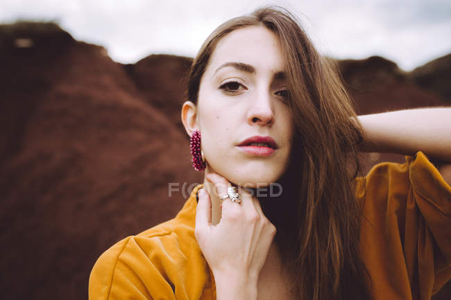 Portrait of brunette in yellow jacket posing on shore — Stock Photo