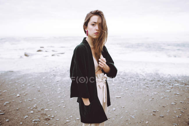 Stylish girl in trendy black jacket looking unemotionally at camera on background of ocean in motion. — Stock Photo