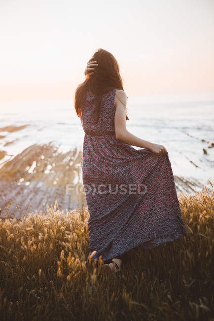 Tender girl in dress walking on field at shoreline — Stock Photo