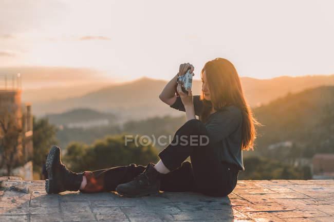 Вид сбоку на женщину, делающую снимки на смотровой площадке при солнечном свете — стоковое фото