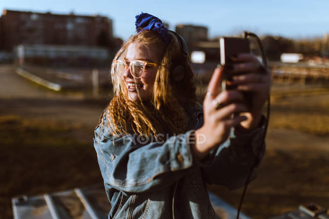 Smiling curly woman in headphones taking selfie in sunset light — Stock Photo