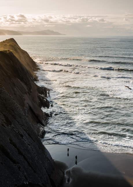 Люди, що йдуть на піщаному пляжі в рок-на березі моря. — стокове фото