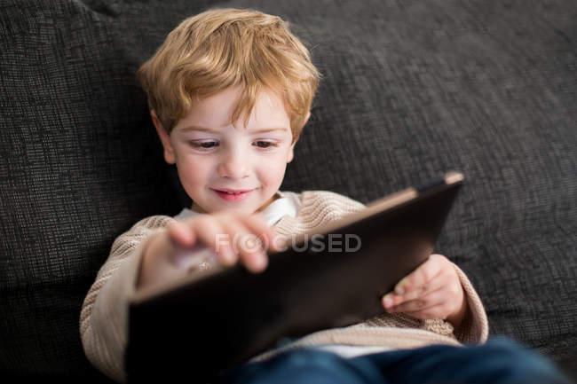 Sorridente ragazzo carino giocare con tablet — Foto stock