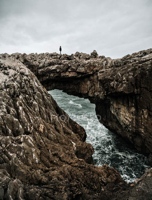 Side view of tourist standing on natural rock bridge at seaside. — Stock Photo