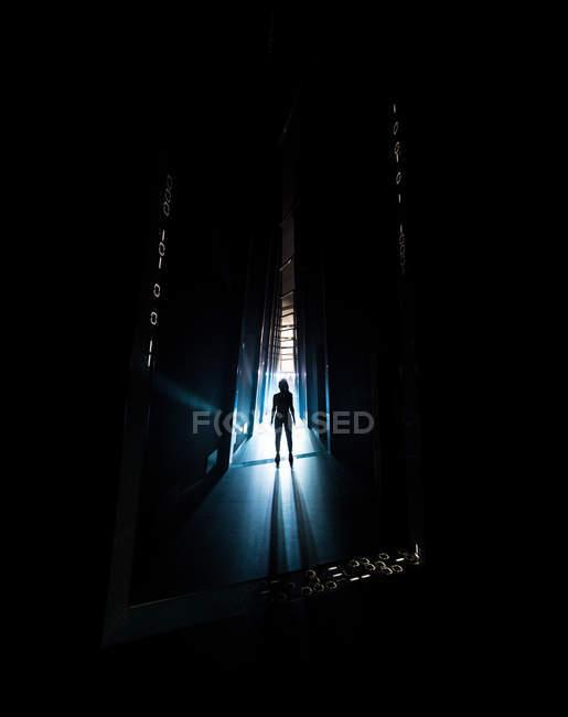 Silueta espeluznante de la persona de pie en el pasillo oscuro . - foto de stock