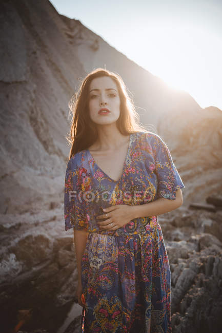 Portrait of brunette in colorful dress looking at camera in sunlight. — Stock Photo