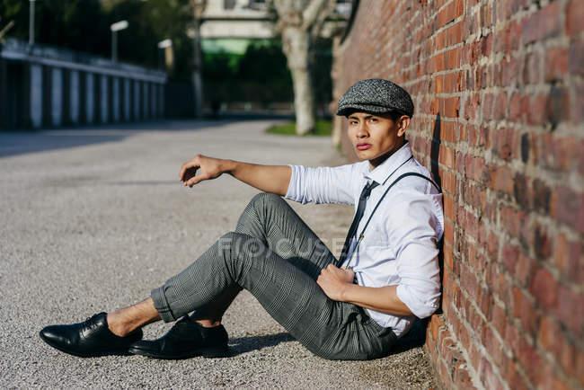 Fashionable man in vintage cap sitting at brick wall — Stock Photo
