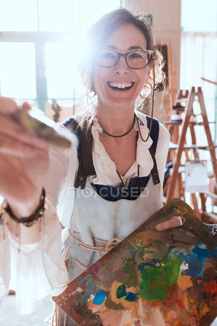 Cheerful  woman with brush and palette drawing in workshop. — Stock Photo