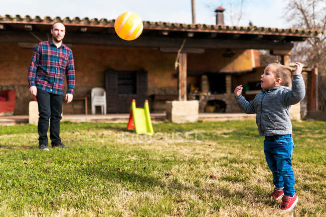 Молодий хлопчик і батько гра з м'ячем на задньому дворі удома — стокове фото