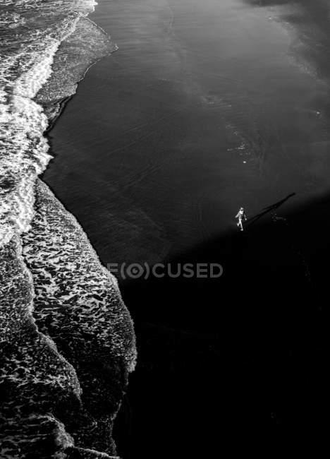 Висока кут зору людину, що йде на мокрій пляжі біля океану. — стокове фото