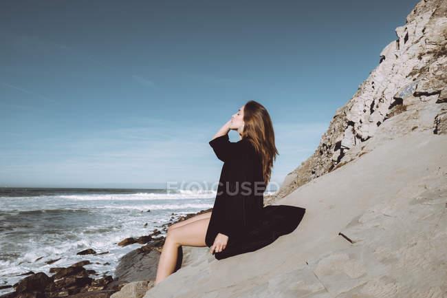 Side view of brunette in black coat on coastline — Stock Photo
