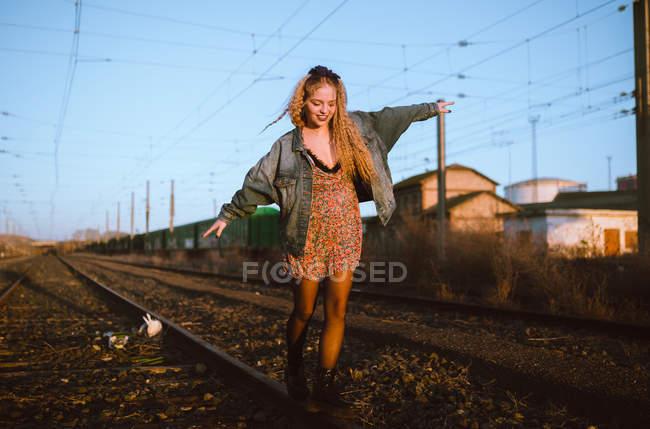 Donna bionda allegra camminando sulla ferrovia e guardando in basso — Foto stock