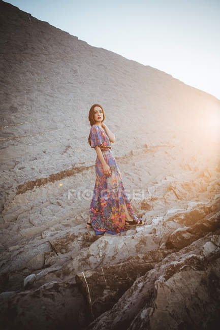 Brunette in dress with floral pattern posing on rocky terrain — Stock Photo