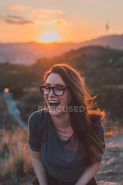 Portrait of brunette girl in glasses laughing in sunset light — Stock Photo