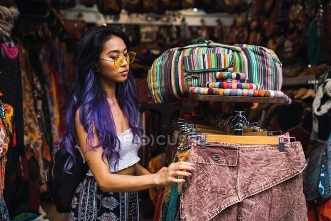 Donna graziosa con capelli viola in posa nel negozio di vestiti — Foto stock 483e1e3b2c1