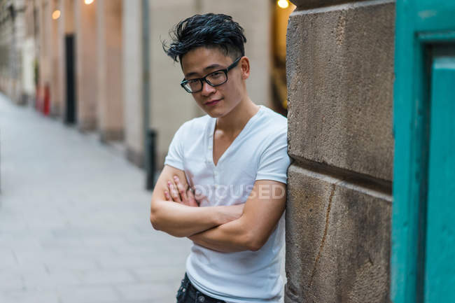 Man in white t-shirt and glasses standing with hands crossed on street — Stock Photo