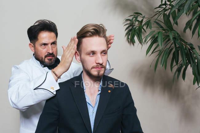 Coiffure coiffeur de jeune homme en costume dans le salon de coiffure . — Photo de stock