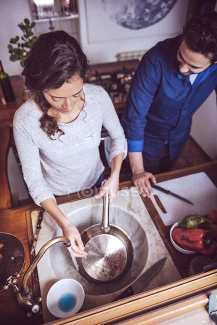 Высокий угол обзора мытья посуды супружеской парой — стоковое фото