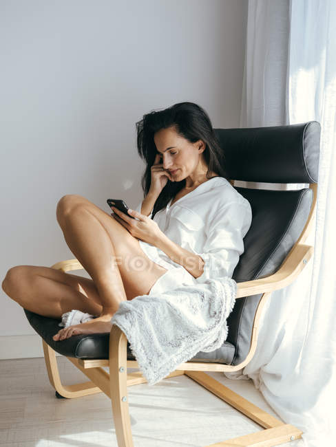 Brunette woman sitting in armchair and using smartphone at home. — Stock Photo