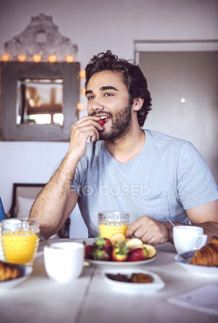 Happy man having breakfast at kitchen — Stock Photo