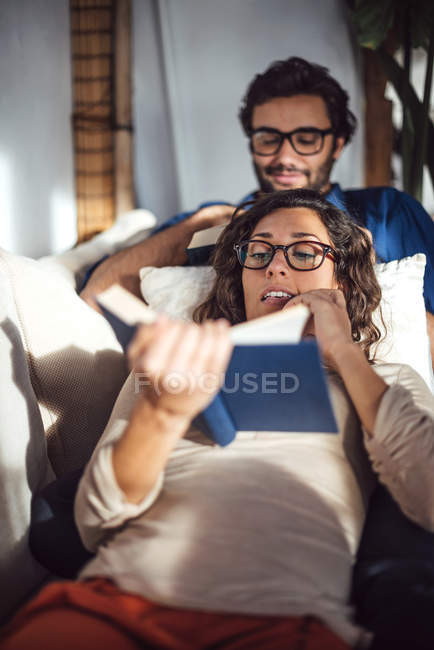 Young couple reading book on couch at home — Stock Photo