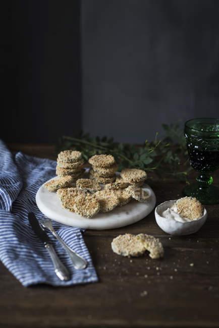 Tranches de courgettes frites dans de la chapelure servie avec un bol de sauce trempette sur la table . — Photo de stock