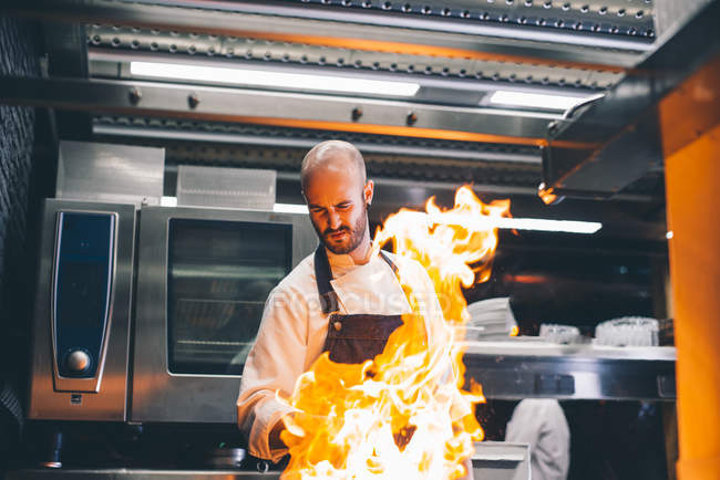 Fire flame over cook making flambe in restaurant — Stock Photo