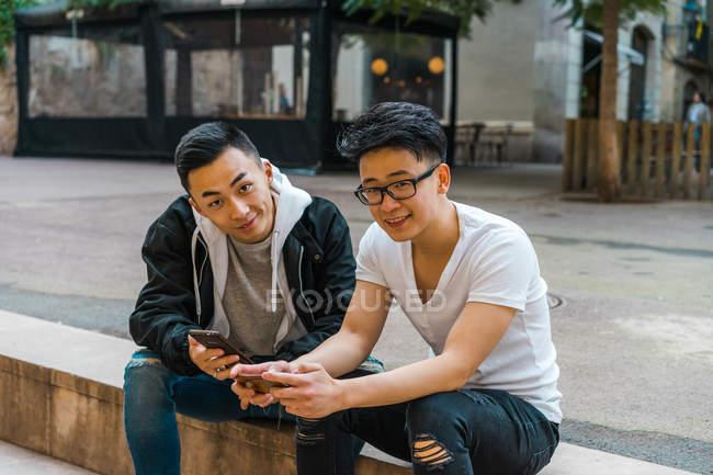 Молодые ребята сидя на улице и с помощью телефона — стоковое фото