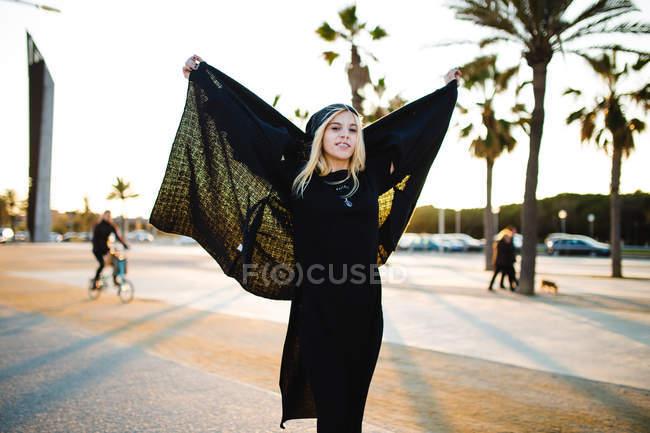 Stylish woman posing with warm jacket at sunlit street — Stock Photo