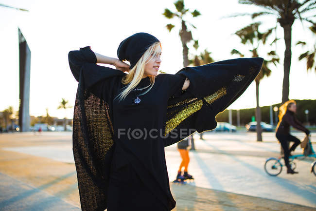 Blonde woman putting wearing warm jacket and posing on boulevard in sunny day. — Stock Photo