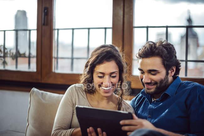 Молодая пара, сидящая на диване и пользующаяся планшетом — стоковое фото