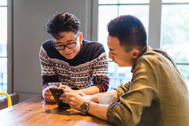 Двое молодых людей обмена смартфон и отдохнуть в кафе, имея напитки. — стоковое фото