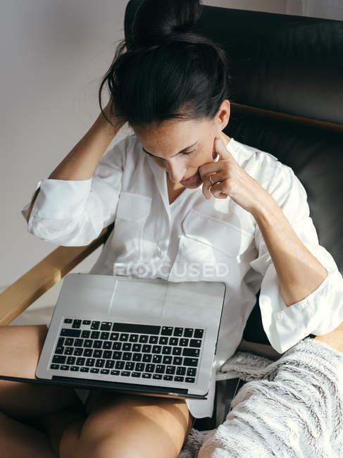 Продуманий брюнетка жінка сидить у крісло і дивляться ноутбук на дому. — стокове фото