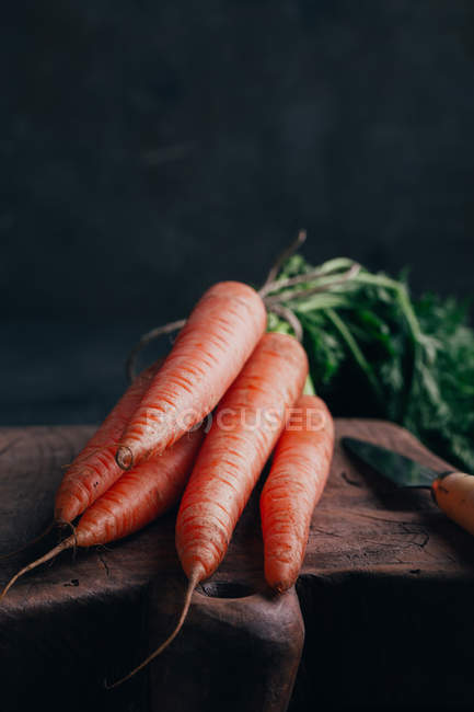 Fresh carrots on wooden cutting board — Stock Photo