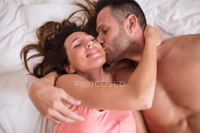 Homme joyeux embrasser petite amie sur le lit — Photo de stock