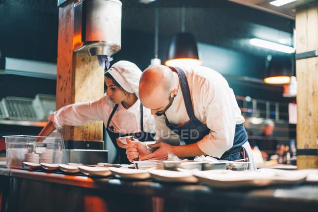 Cuisiniers homme et femme debout au tableau et les assiettes de service avec de la nourriture dans la cuisine — Photo de stock