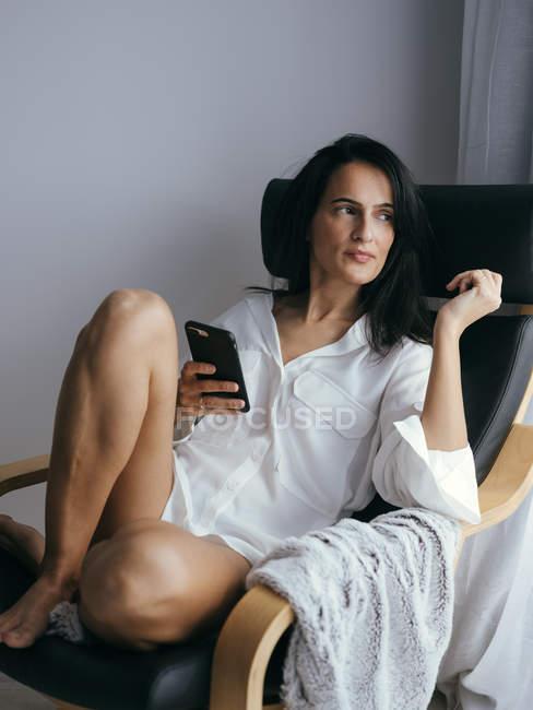 Frau sitzt im Stuhl mit Smartphone und wegsehen — Stockfoto
