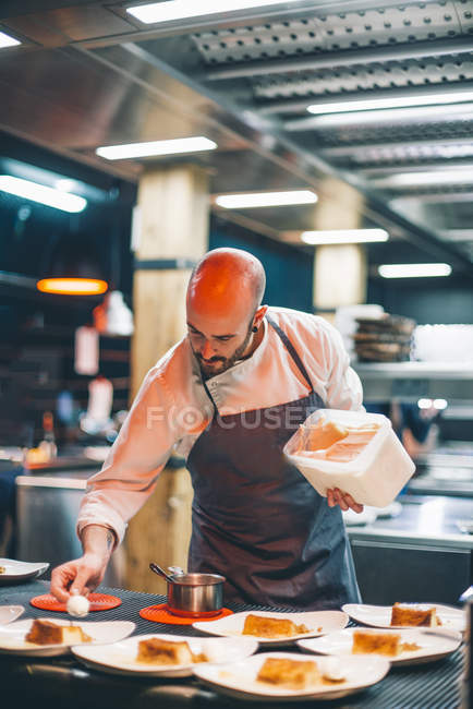 Chef adding sauce on plates at restaurant kitchen — Stock Photo